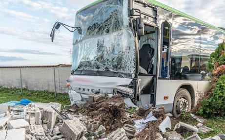 Autobus crasht in Gartenmauer